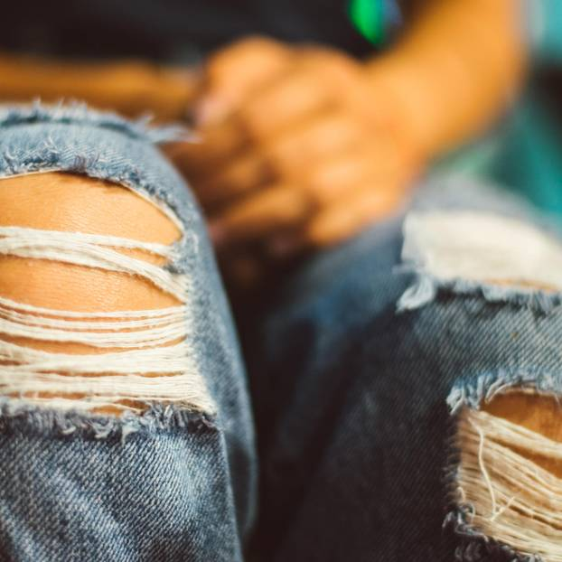 Frauenbeine in einer Jeans mit Löchern an den Knien