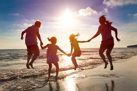 Blau machen: Familie hüpft am Strand