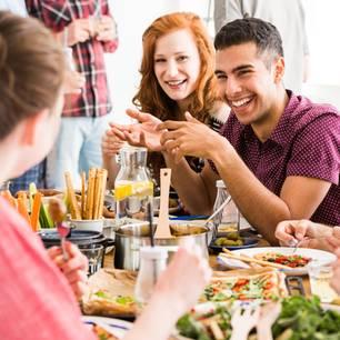 Lecker helfen: Freunde sitzen beim Essen zusammen