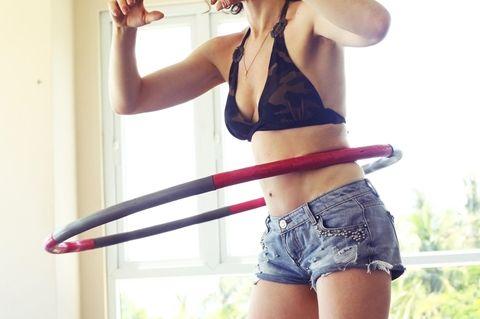 Hula-Hoop: Frau schwingt einen Reifen um ihre Hüfte