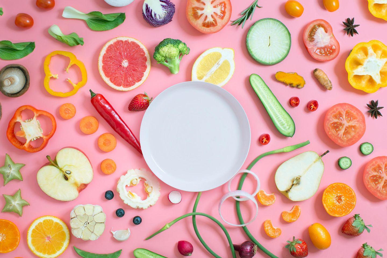Teller auf pinkem Hintergurnd und viel Obst und Gemüse