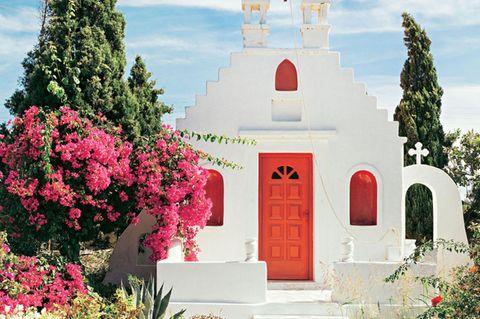 Mykonos Reisetipps: Privatkapelle mit weißer Mauer und roten Türen und Fenstern