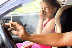 Rauchen im Auto: Frau raucht im Auto mit Kind an Bord
