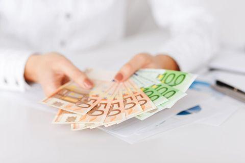 Finanzberatung für Frauen: Ausschnitt von zwei Händen mit Geldscheinen