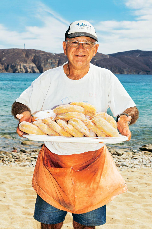 Mykonos Reisetipps: Mann am Strand mit einem Tablett voller Süßwaren