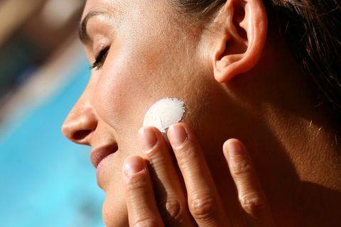 Sonnencreme fürs Gesicht: Frau cremt sich mit Sonnencreme im Gesicht ein