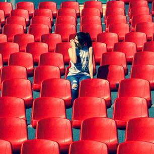 Alleine ausgehen: Frau sitzt in leerem Publikum
