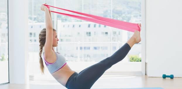 Theraband-Übungen: Eine Frau trainiert mit einem Theraband