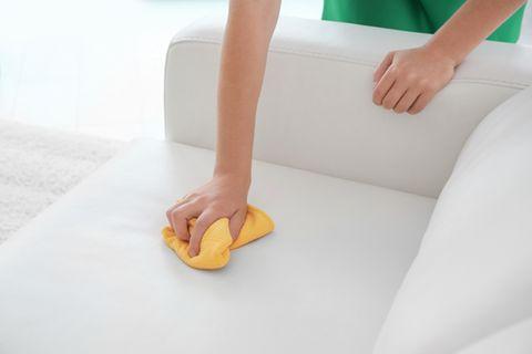 Wasserflecken entfernen: Frau reinigt Sofa
