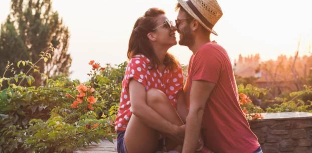 Geheimnis glücklicher Beziehungen: Ein Pärchen sich anlächelnd an eine Mauer gelehnt