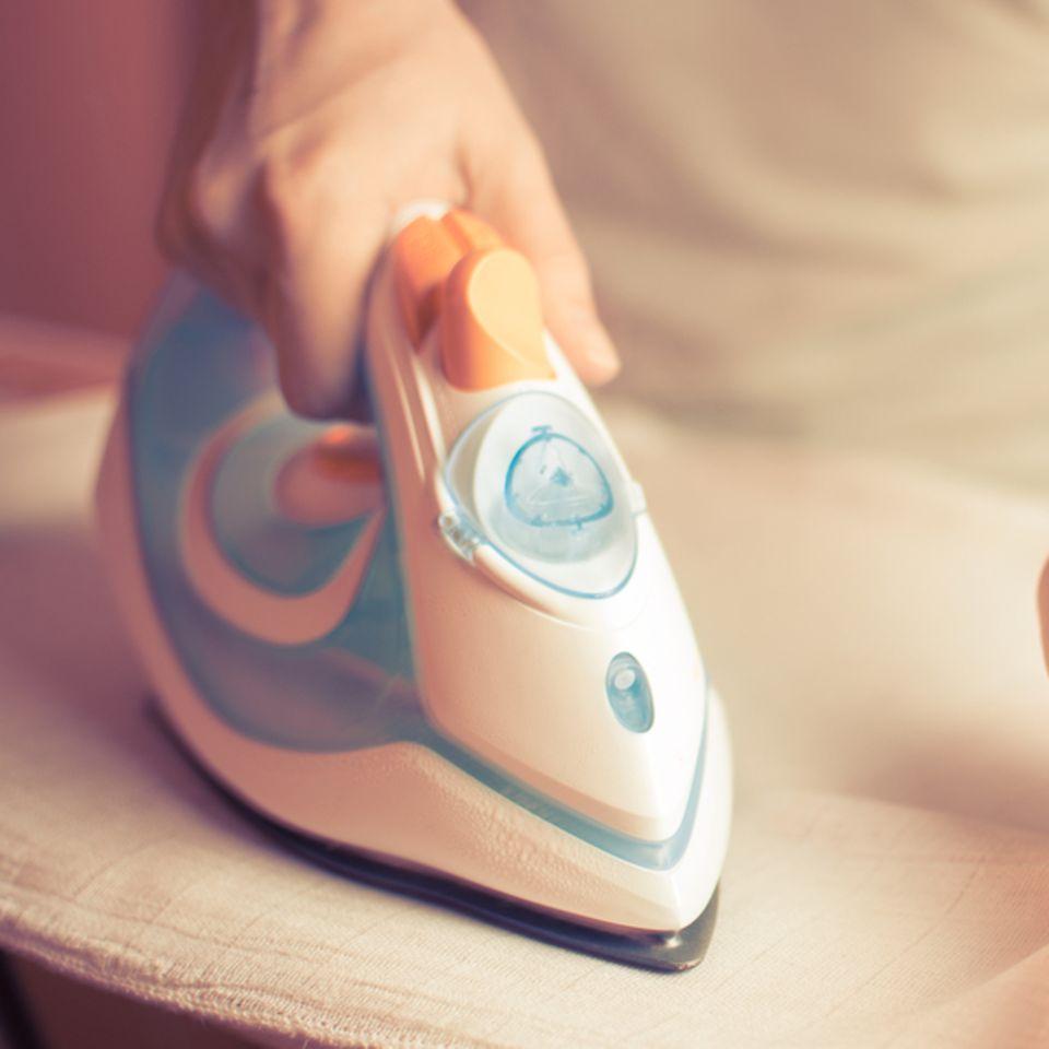 Bügeln: Frau bügelt Decke