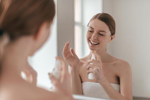 Frau sprüht sich Facial Mist ins Gesicht