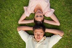 Männliches, weibliches Gehirn: Mann und Frau liegen im Gras
