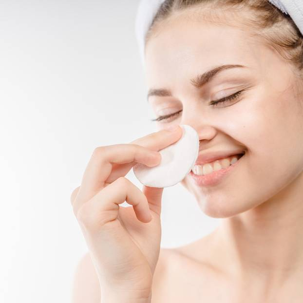 Mizellenwasser: Frau reinigt ihr Gesicht mit Wattepad