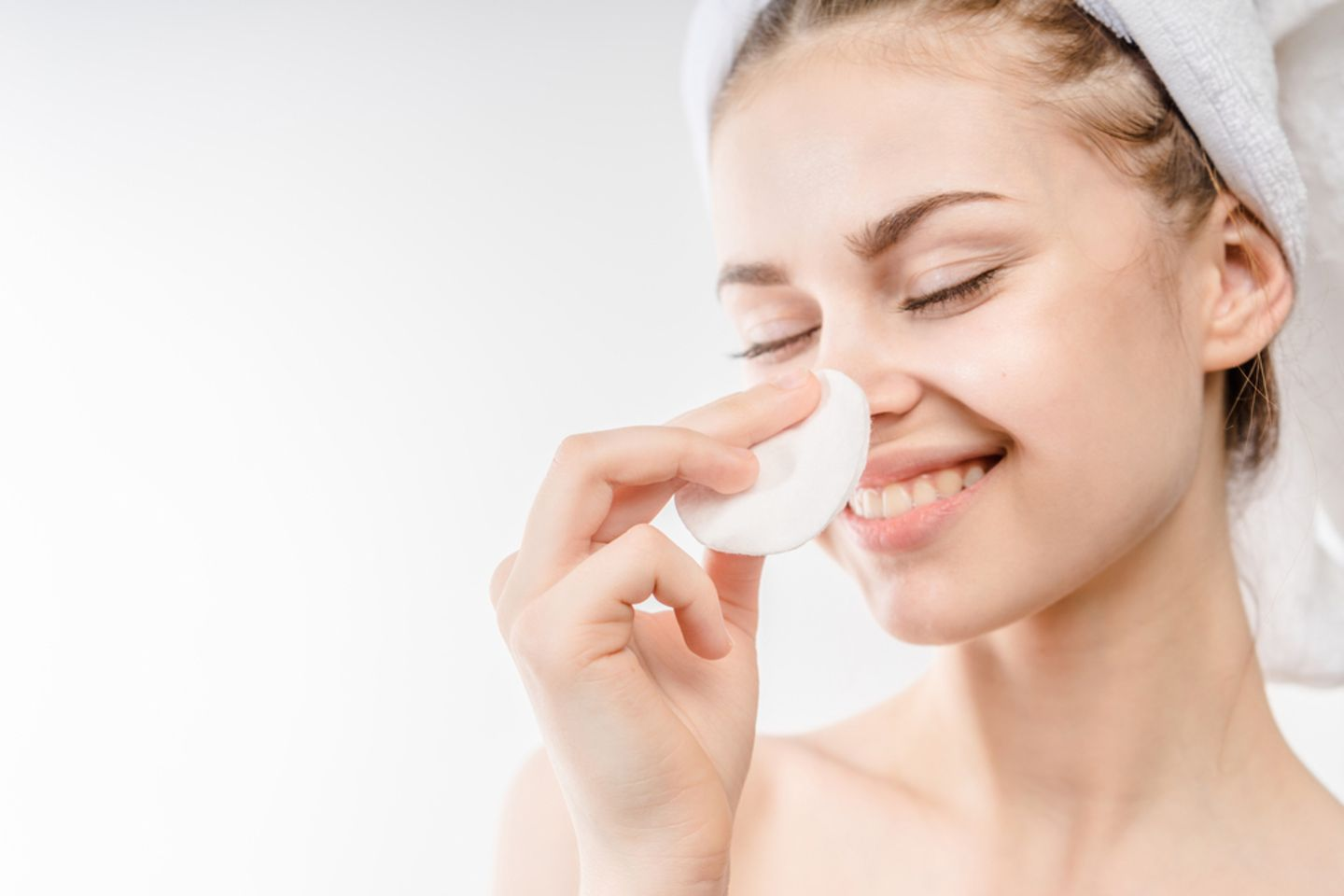 Micellar water: woman cleans her face with a cotton pad