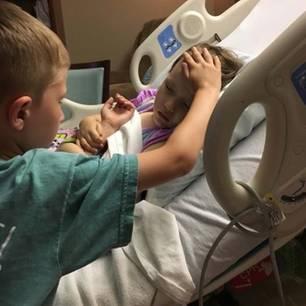 Der 6-jährige Jackson Sooter hält seiner sterbenden Schwester die Hand