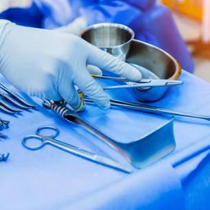 Chirurgen-Hand greift nach OP-Besteck
