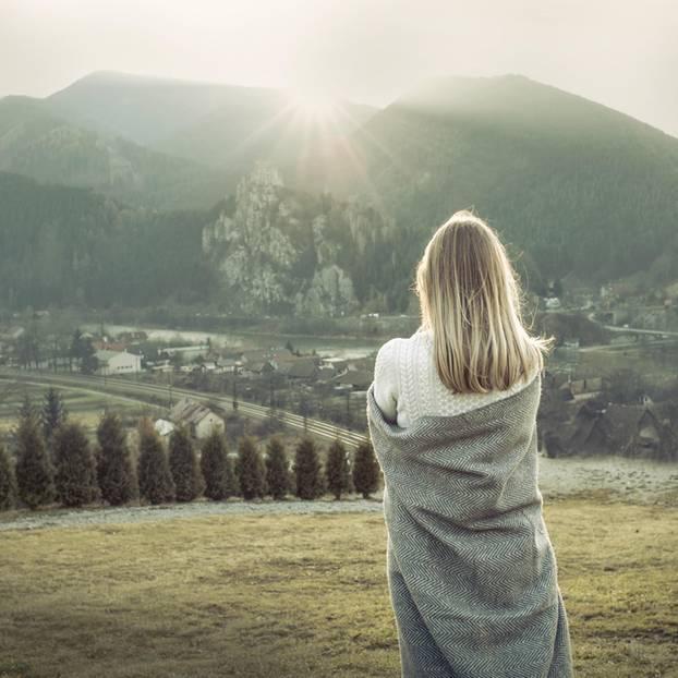 Eine Frau vor einer Bergkulisse mit Decke um den Rücken gehängt