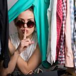 Eine Frau versteckt sich zwischen Kleidern und legt den Finger auf den Mund