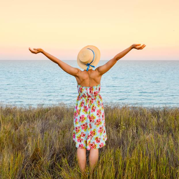 Achseln rasieren: Frau steht am Meer und reißt die Arme hoch