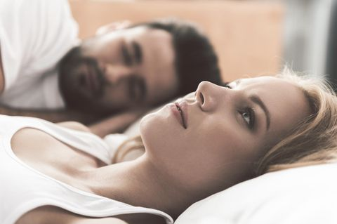 Soll ich Schluss machen? Frau liegt im Bett und denkt nach, während Partner neben ihr schläft