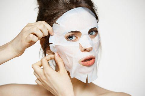 Frau trägt Gesichtsmaske auf