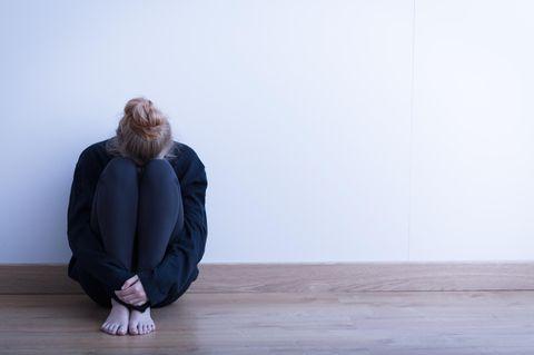 USA: Eine Frau sitzt zusammengekauert mit dem Rücken zur Wand