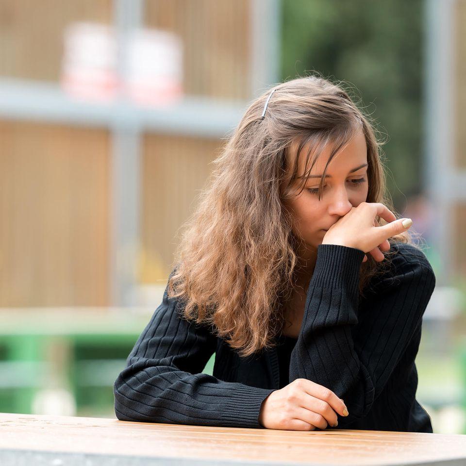 Intelligenz: Eine junge Frau senkt bedrückt den Blick
