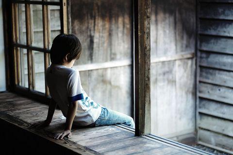 Studie: Ein deprimierter kleiner Junge mit gesenktem Kopf am Fenster