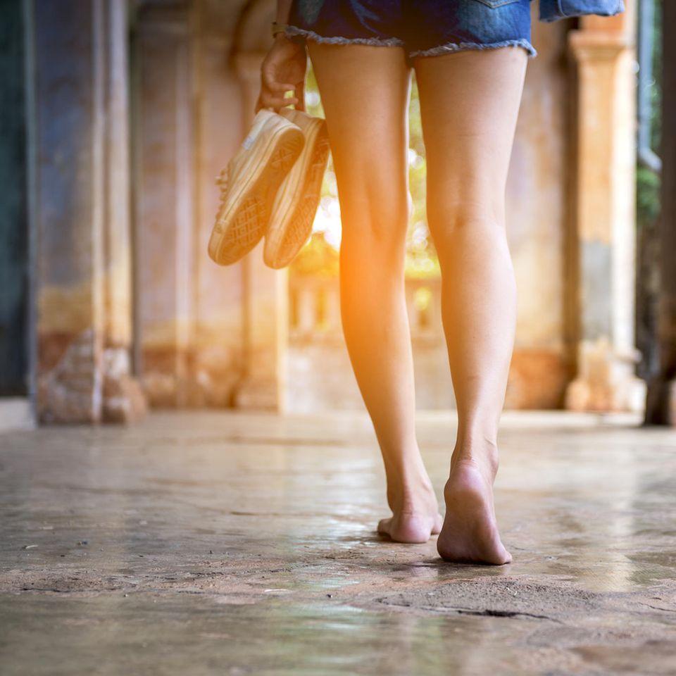 Barfuß laufen: Frau läuft ohne Schuhe