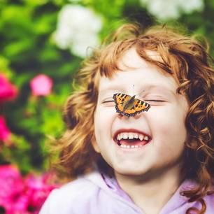 Ein lachendes kleines Mädchen mit einem Schmetterling auf der Nase