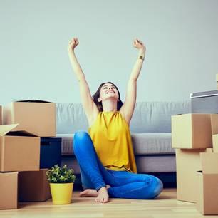 Umzug Checkliste: Frau mit Umzugskartons in neuer Wohnung