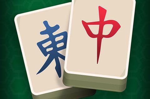 Mahjong: Traditionelle Spielsteine vor grünem Hintergrund