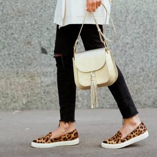 Sommertaschen: Frau mit beigefarbener Handtasche und Leoparden-Schuhen