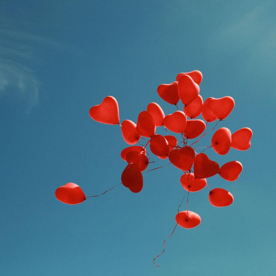 Offene Liebe: Rote Herzchen-Luftballons fliegen in den blauen Himmel