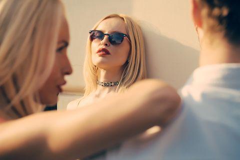 Eifersucht bekämpfen: Eine eifersüchtige Frau beobachtet ein Paar