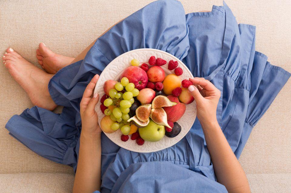 Obstflecken entfernen: Frau isst Obst