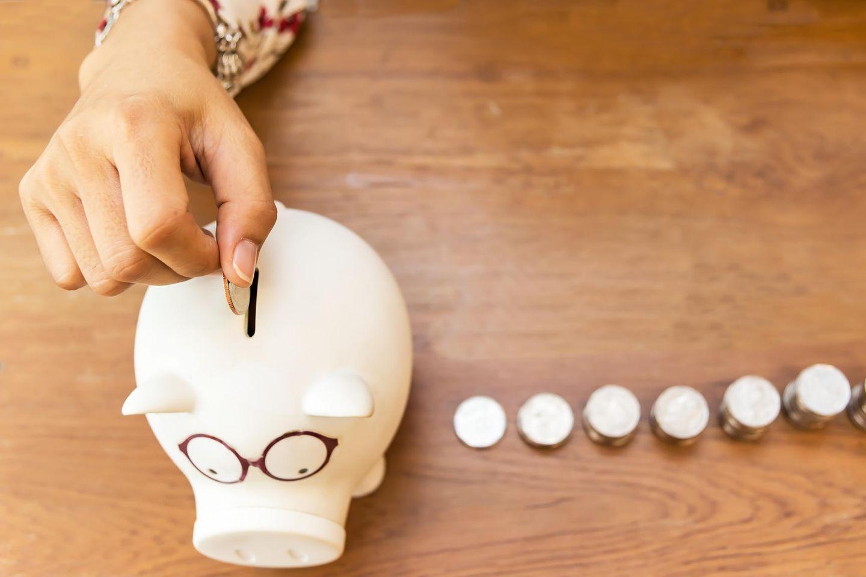 Sparen im Alltag: Frau wirft Geld in Sparschwein