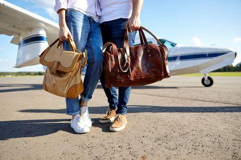 Twitter: Pärchen mit Reisetaschen vor einem Flugzeug