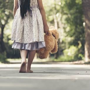 Lieblose Kindheit: Mädchen läuft barfuß auf der Straße und hält Teddy