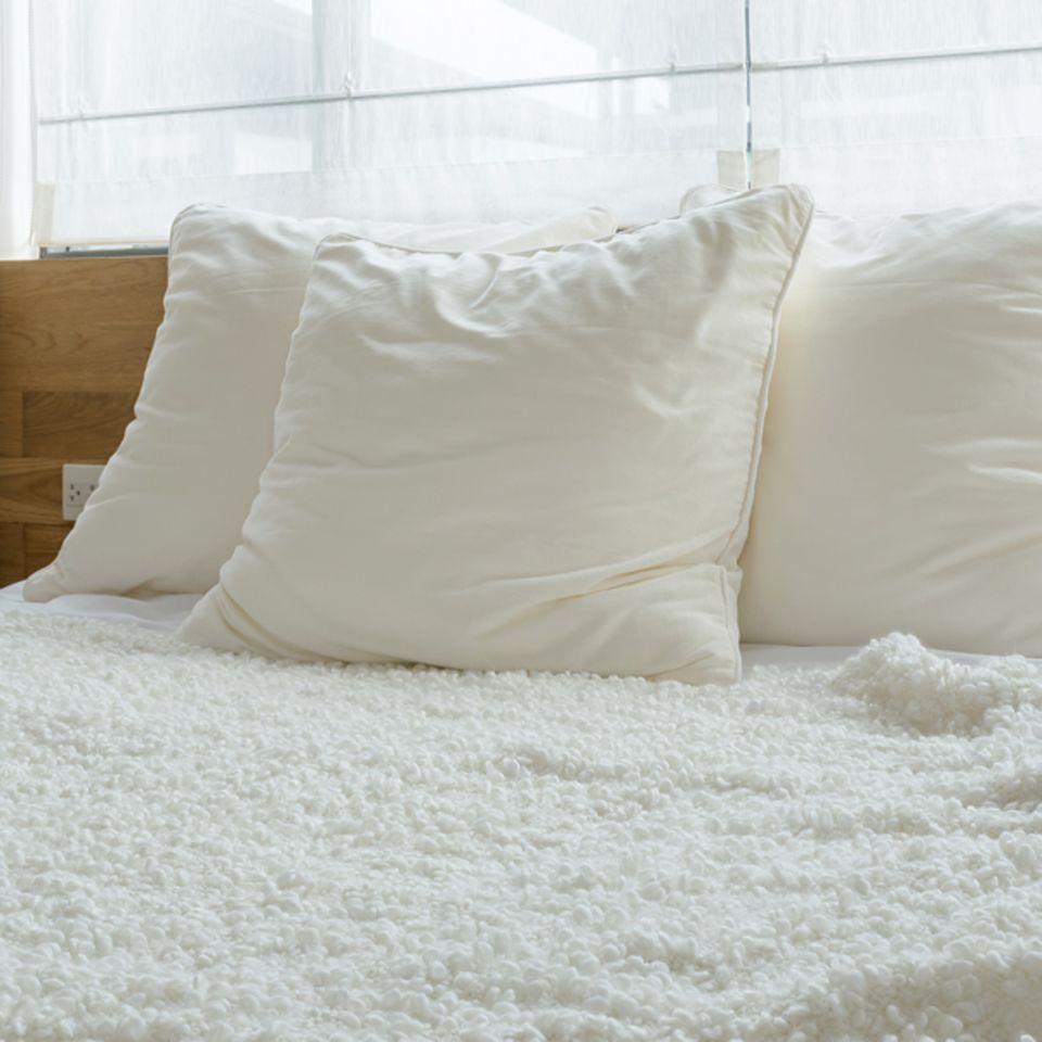 Daunenkissen waschen: Daunenkissen auf dem Bett