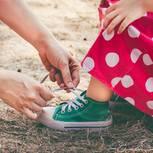 Zeitsparen mit Kindern: Mutter bindet ihrer Tochter de Schuhe