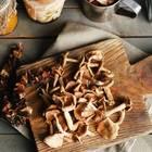 Pilze trocknen: Getrocknete Pilze auf einem Schneidebrett