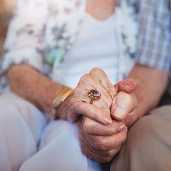 Altes Paar hält Händchen