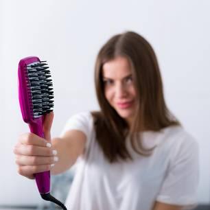 Glättungsbürste: Frau glättet sich die Haare