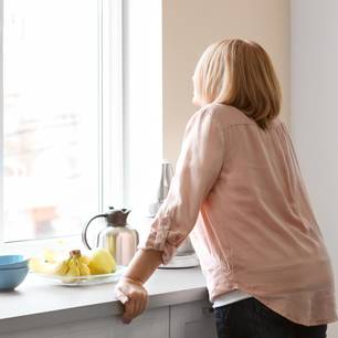 Empty Nest Syndrom: Einsame Frau steht in der Küche und sieht aus dem Fenster