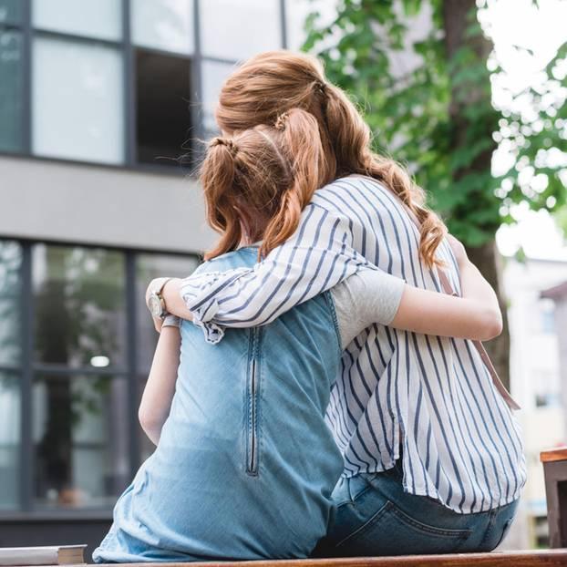 Als Mutter Vollzeit arbeiten: Mutter umarmt Tochter auf einer Bank