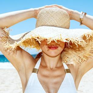 Sommer-Beauty-Hacks: Frau mit Hut am Strand