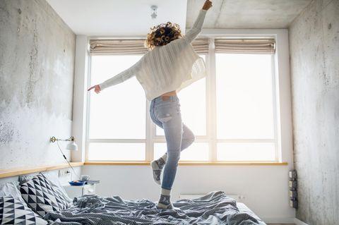 Eine Frau tanz auf ihrem Bett