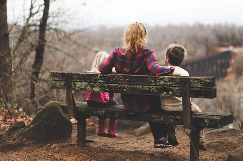 Abtreibung: Frau sitzt mit zwei Kindern auf einer Bank